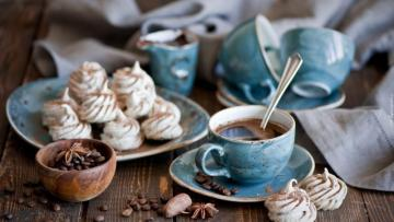 deser that c.d - a cup of coffee and meringues on a plate