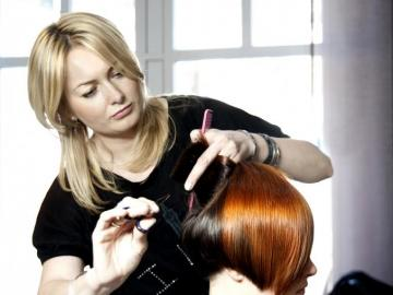 Hairstylist in action - The picture shows the lady hairdresser when cutting hair to the client.