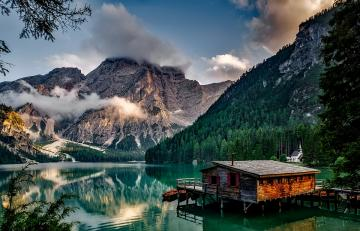 A mountain view - Lake, mountains, house and forest.