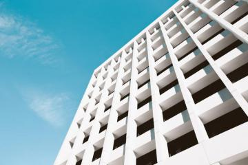 Bright white building facade - Low angle photography of white building under blue sky. Chicago
