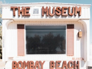 THE MUSEUM in Bombay Beach - White and brown wooden building.