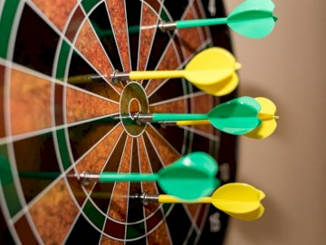 Close up of magnetic darts on - Green, red, and yellow dartboard. Pennsylvania