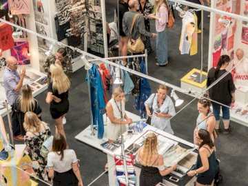 New Designers London. - Group of people gather in clothes stores. London