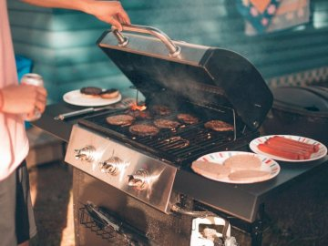 Snapped a photo of a friend - Person cooking burger on gas grill. Toronto