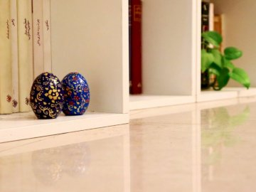 Kashan souvenir - Blue and white floral egg ornament on white wooden cabinet.